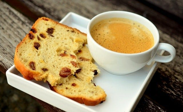 Scheibe Rosinenbrot an Kaffee in weißem Kaffeeservice mit quatratischer Untertasse.