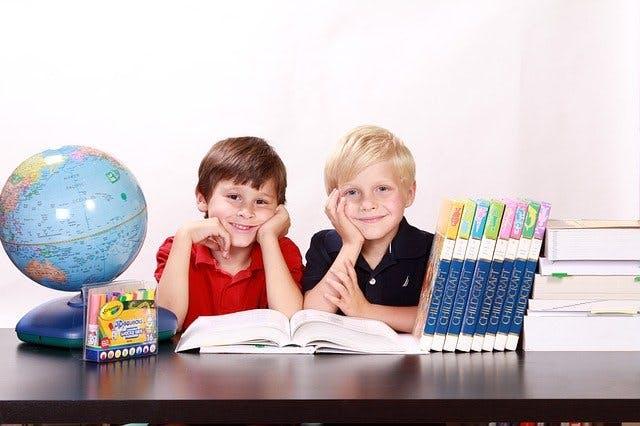 zwei Kinder mit Globus und Büchern