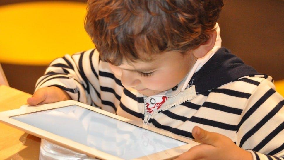 Ein Kind schaut auf den Bildschirm eines Tablets