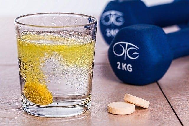 Wasserglas mit Vitamintablette neben einem Paar leichter Kurzhanteln.