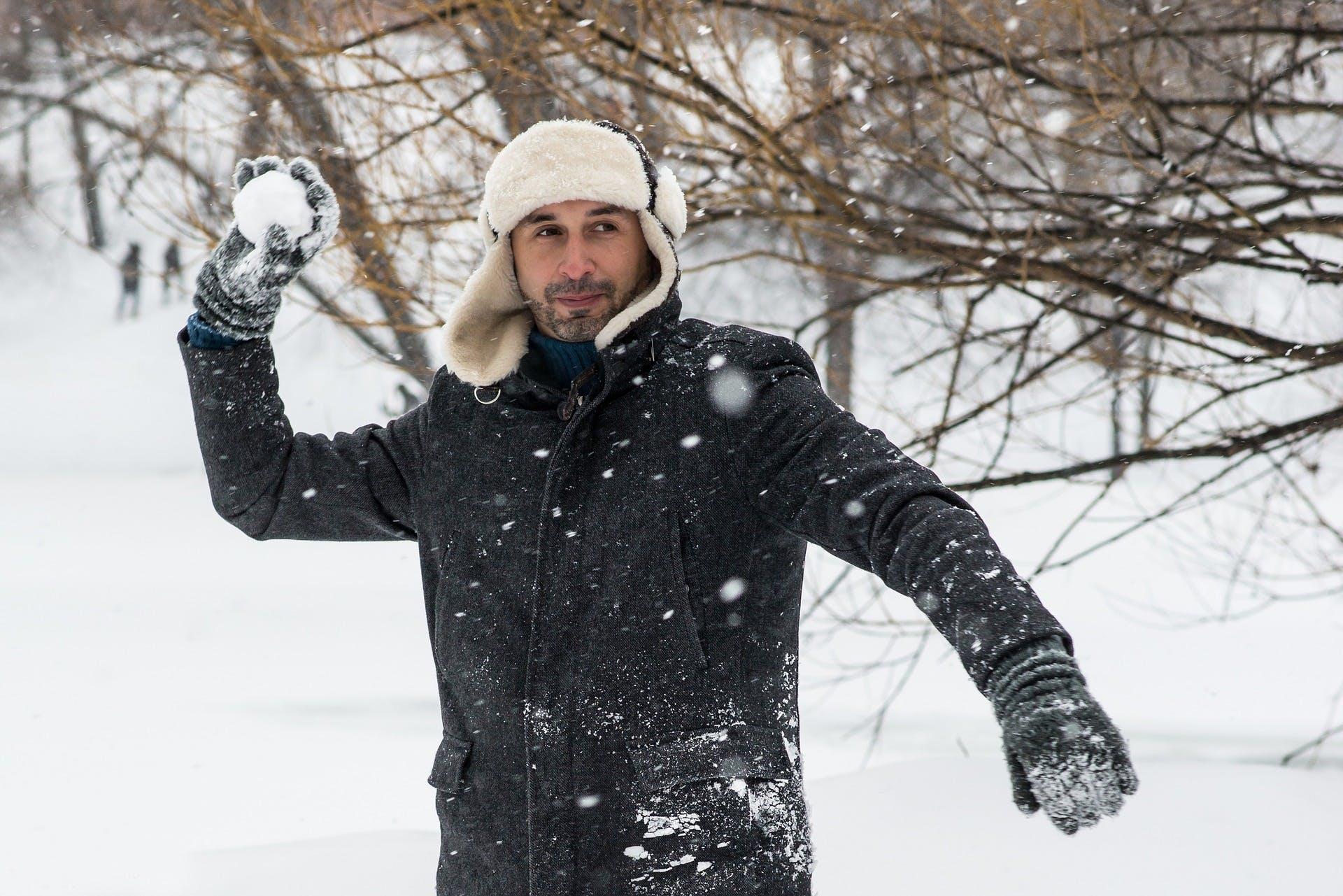 Mann wirft Schneeball