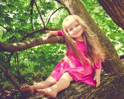 Kleines Mädchen sitzt auf einem Baumstamm