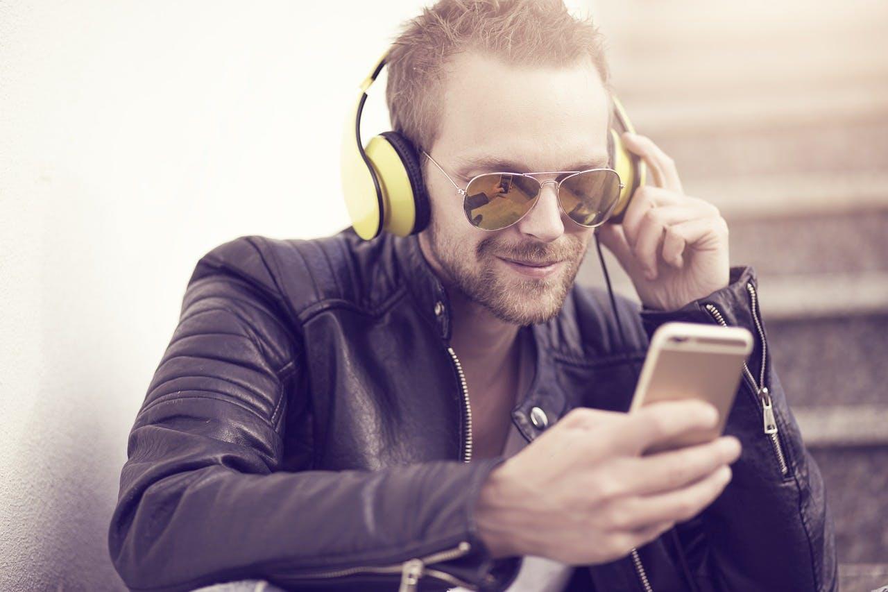 Mann in Lederjacke und mit Sonnenbrille auf hört Musik über sein Handy