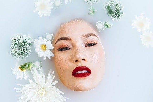 Frauengesicht taucht in milchigem Wasserbad zwischen Blüten auf