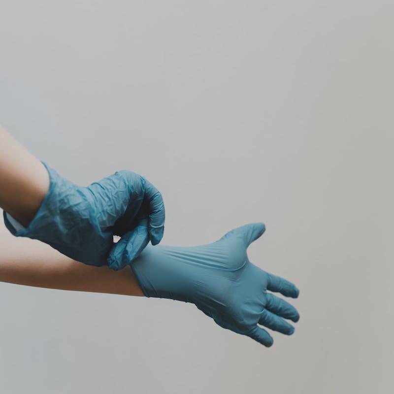Person zieht blaue Gummihandschuhe an