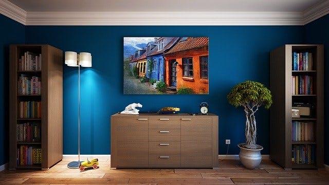Blaue Wand mit Bild, Kommode, Pflanze, Bücher