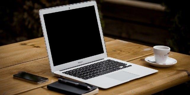 Neben einem weißen Laptop stehen ein Espresso, ein Smartphone und ein Notizblock