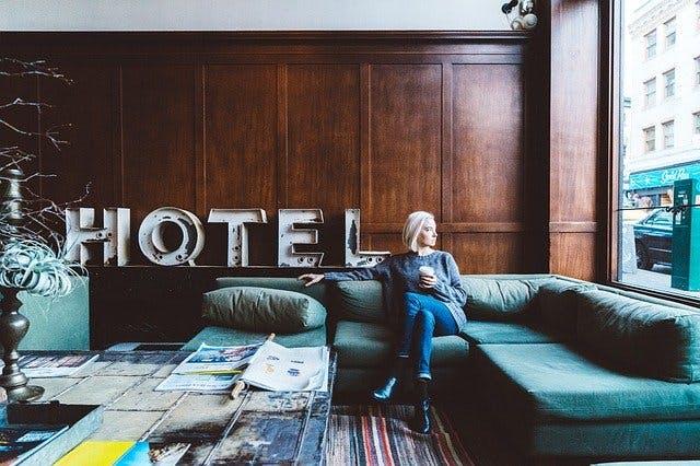 Frau sitzt in Hotel Lobby