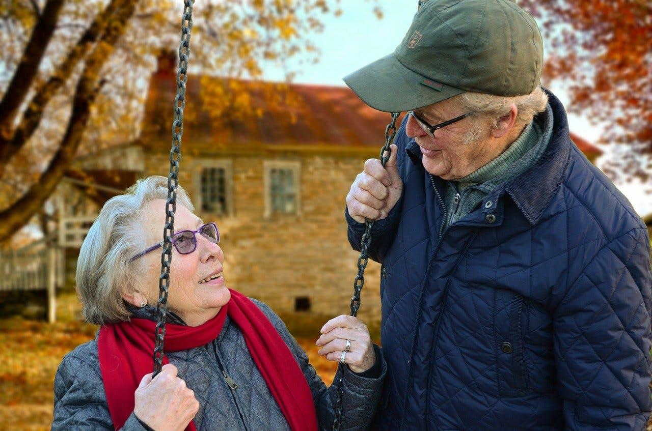 Oma sitzt auf einer Schaukel und schaut Opa verliebt in die Augen