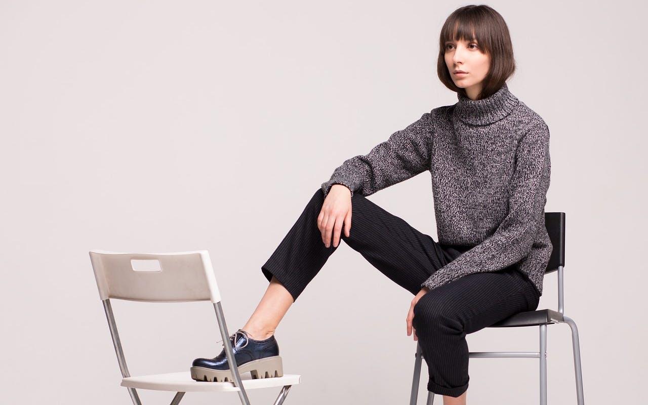 Frau in grauem Pullover sitzt auf hohem Stuhl, den einen Fuß hat sie auf niedrigeren Stuhl gestellt