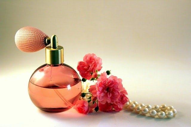 Parfumflasche, Perlenkette und Blumen