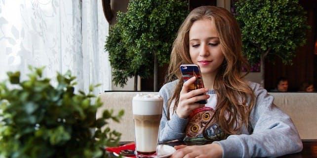 Frau sitzt mit Smartphone im Cafè