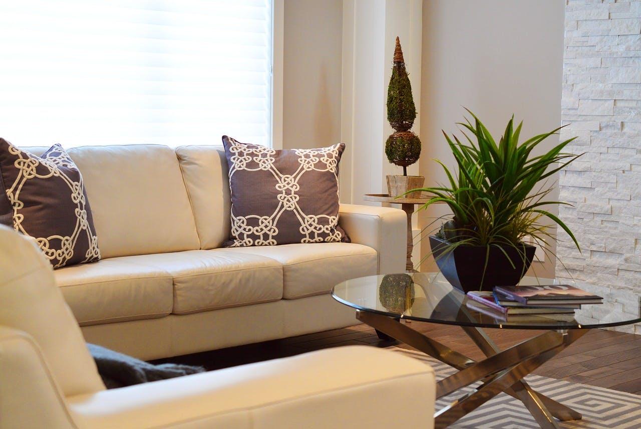 Beige Couchecke in hellem Wohnzimmer mit rundem Glastisch und Zimmerpflanzen