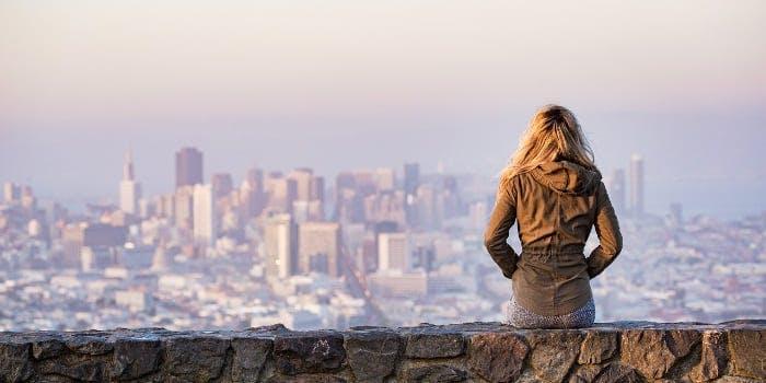 Frau blickt auf die Skyline einer Stadt herunter