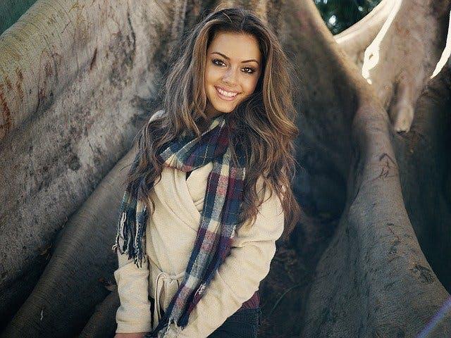 Model lächelnd vor Baum