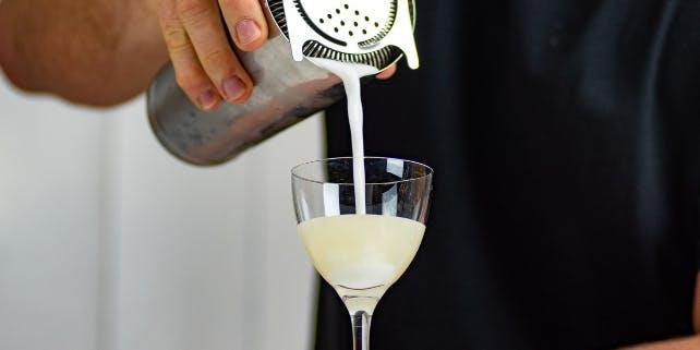 Barkeeper gießt einen Cocktail aus dem Shaker