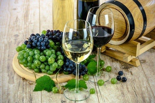 zwei Gläser Rot- und Weißwein stehen vor einem Fass und Weintrauben
