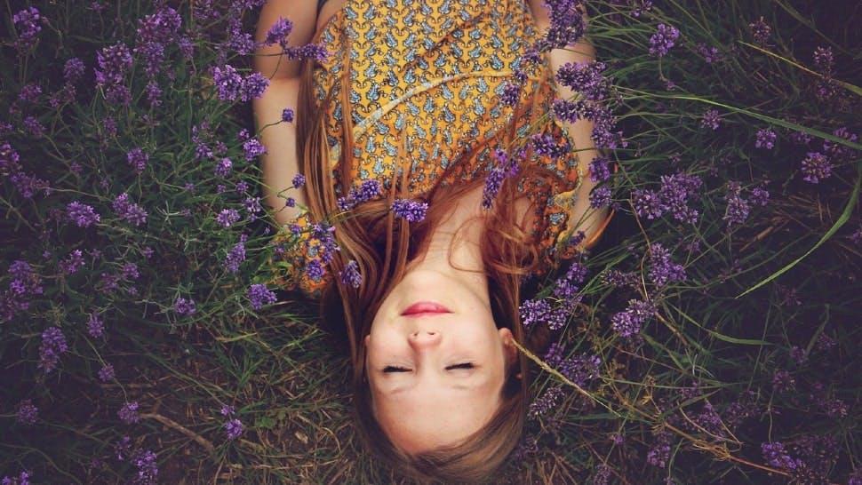Ein Mädchen liegt mit geschlossenen Augen in einem Lavendelfeld