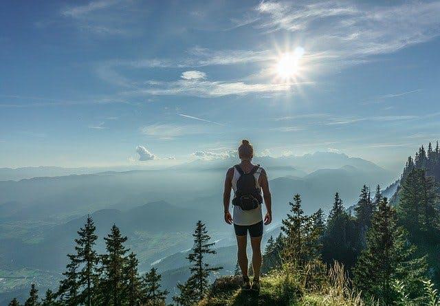 Wanderin steht an einem bewaldeten Berghand im Sonnenschein.