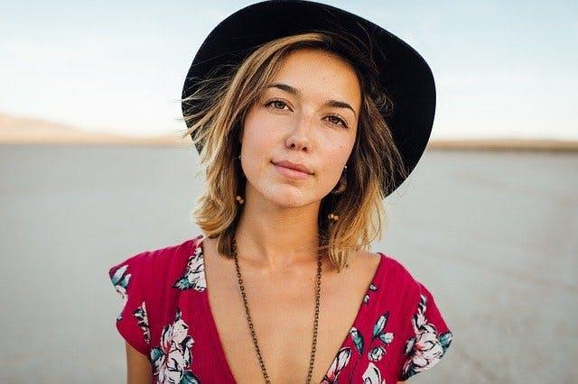 Portrait von Frau mit Hut und Sommerkleid.