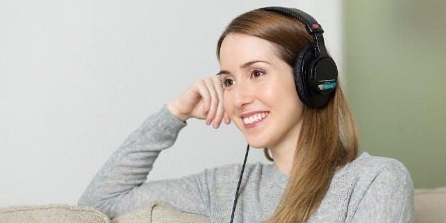 Frau hört mit Kopfhörern einen Podcast