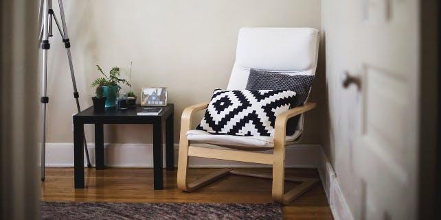 Sessel mit Kissen, daneben Tisch mit Pflanzen und Foto