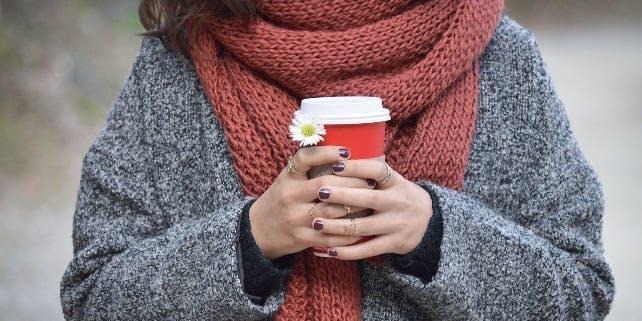 Frau mit dickem Schal und Becher in der Hand