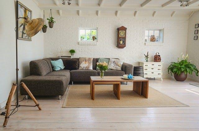 Modern eingerichtetes Wohnzimmer. Mit hellen Wänden grauer Sitzecke hinter Holztisch.