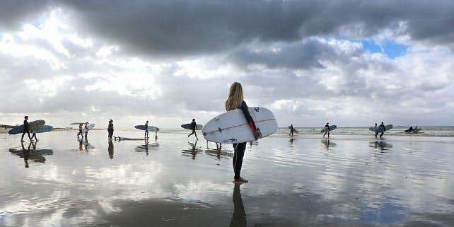 Eine Gruppe von Surfern geht ins Meer