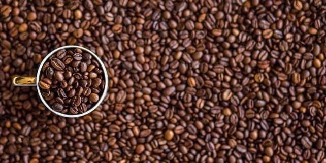 Kaffeegenuss: Tasse umzingelt von Kaffeebohnen