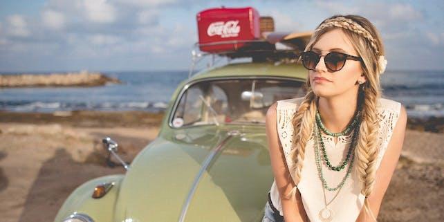 Blondine lehnt an ihrem Auto vor einem Strand