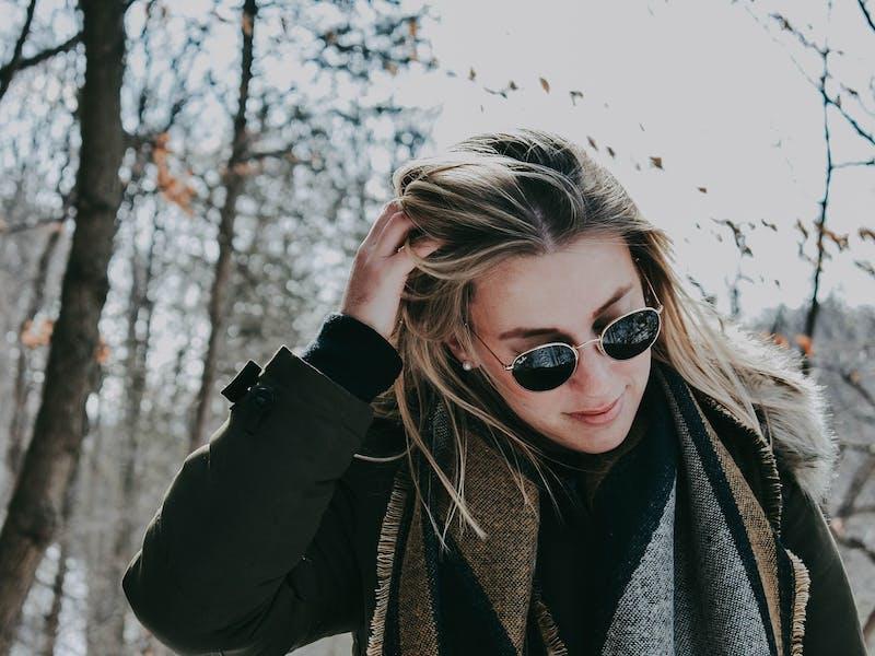 Frau mit Sonnenbrille, Schal und dunkler Jacke im Wald
