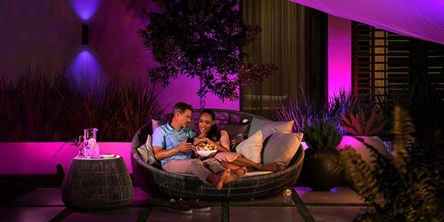 Paar sitzt gemütlich auf der Terrasse, rings herum ist pinkes Licht