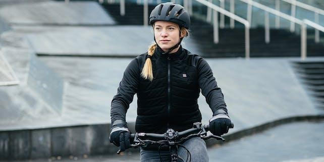 Schwarz gekleidete Frau mit Helm und Handschuhen auf dem Fahrrad