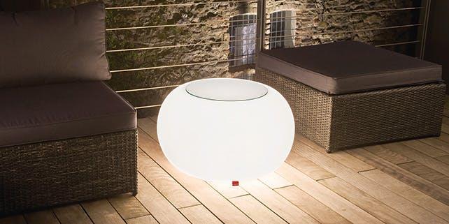 Leuchtender Beistelltisch zwischen Sitzmöbeln auf der Terrasse