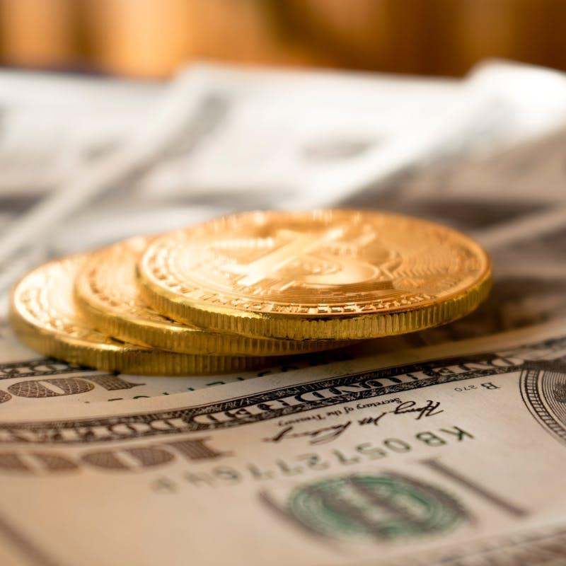 Goldmünze liegt auf Geldschein.