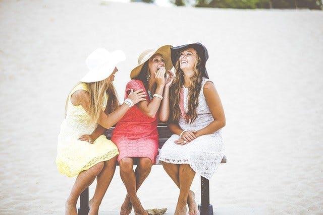 Drei Frauen mit Hüten und bunten Sommerkleidern auf Sitzbank am Strand.