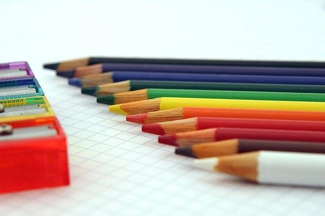 Buntstifte und Bleistiftspitzer in Regenbogenfarben