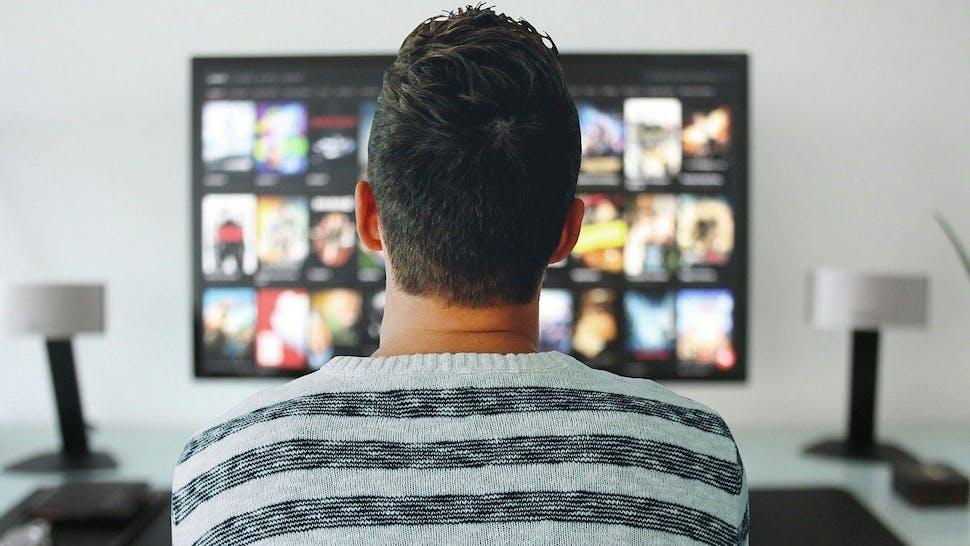 Mann sitzt vor seinem Smart TV