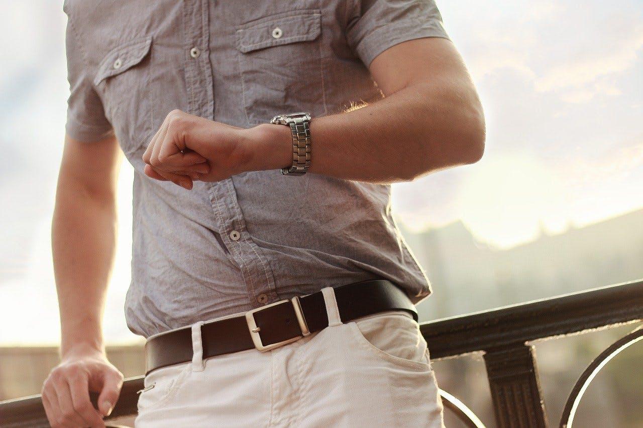 Mann schaut auf seine Armbanduhr