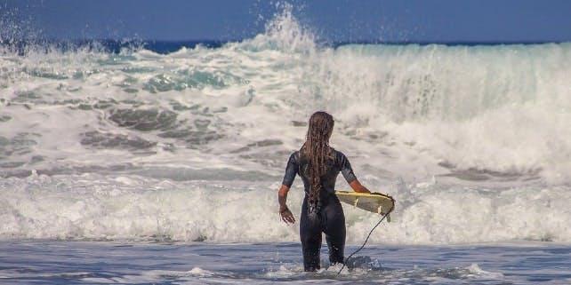 Eine Surferin geht bei einem Surfspot in Europa ins Wasser