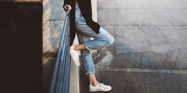 Frau in Jeans und Strickjacke lehnt am Geländer
