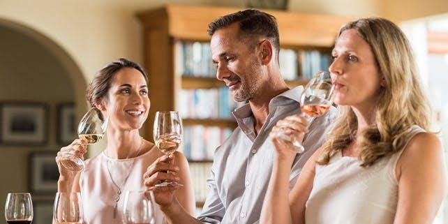 Ein Mann und zwei Frauen trinken Weißwein