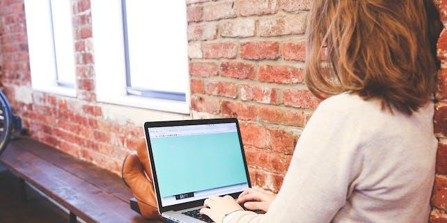 Studentin lehnt an der Wand mit ihrem Laptop auf dem Schoß
