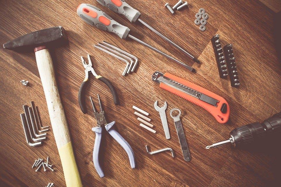 Hammer, Zangen und andere Werkzeuge auf einer Holzoberfläche